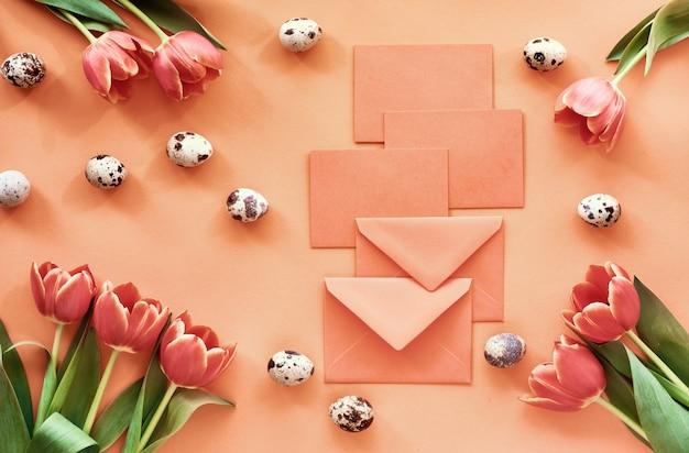 イースターフラットはオレンジ色の紙にチューリップ、ウズラの卵、グリーティングカードを置きます。