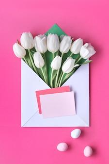 空白のカードと鮮やかなピンクの背景のイースターエッグと紙の封筒の白いチューリップ。