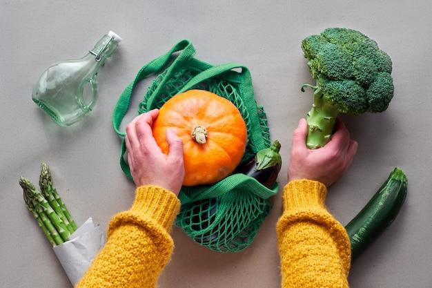 Экологически чистая квартира с нулевыми отходами лежит в руках, держа в руках брокколи и пакет с оранжевой тыквой осенью плоско лежали овощи и руки.