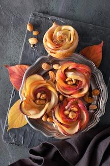 バラの形をしたりんごのスライスを鋳鉄のフライパンで焼き上げたパイと新鮮な赤いリンゴ