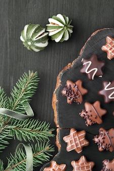 クリスマスツリーの小枝と暗いテクスチャ壁に星形のチョコレート