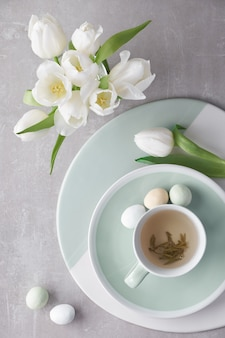 春のフラットはパステルカラー、白いチューリップ、ライトストーンの砂糖イースターエッグで横たわっていた