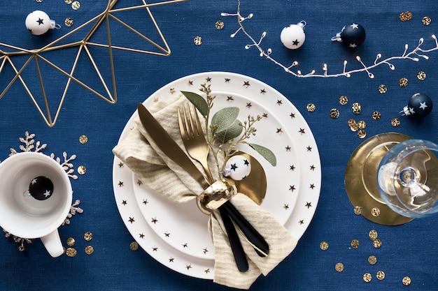 白いプレート、金色の調理器具、金色の幾何学的な金属線の装飾が施されたクリスマステーブルのセットアップ。ダーククラシックブルーのリネンテキスタイルにフラットが横たわっていました。