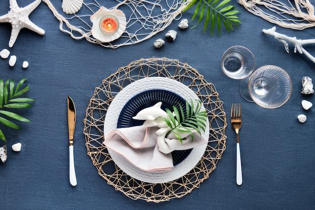 現代的な海のテーブルセッティング、クラシックなブルーのリネンテキスタイルの海の装飾。平面図、コロンバスの日のお祝い。