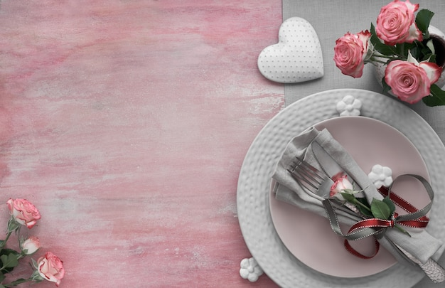 バレンタインデー、誕生日または記念日のテーブルセッティング、淡いピンク色の表面のトップビュー、コピースペース
