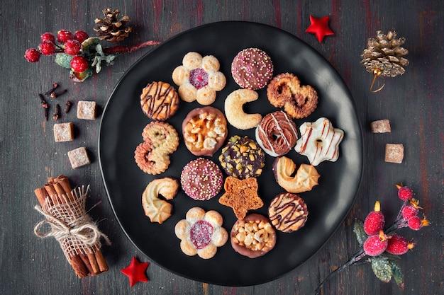スパイスや暗闇の中の装飾と黒いプレートにクリスマスクッキー
