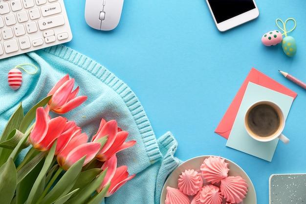 ミント色のセーター、携帯電話、コーヒー、マシュマロのピンクのチューリップ