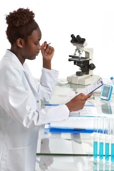 アフリカの生物学者、医学生または医者がオフィスで働いています