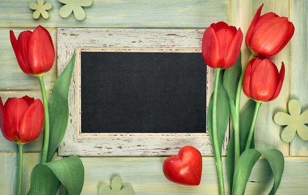 緑の木、あなたのテキストのためのスペースに赤いチューリップで囲まれた黒板