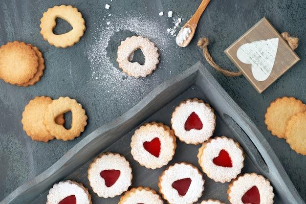 暗闇の中で赤いジャムと伝統的なクリスマスリンツァークッキーのトップビュー