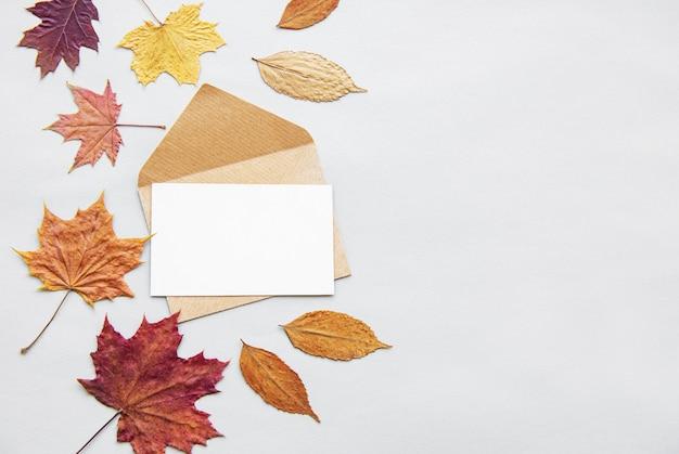 葉、封筒、白い背景の空白カードと秋の組成
