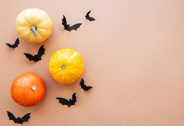 ハロウィーンコウモリと茶色の背景にカボチャ