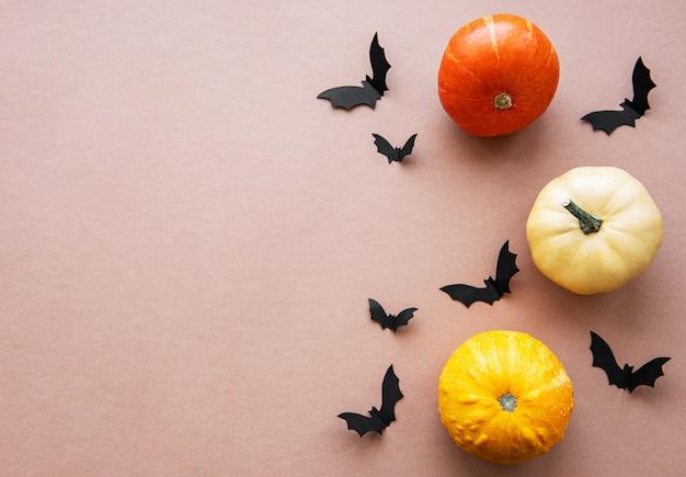 ハロウィーンフライングコウモリと茶色の背景にカボチャ