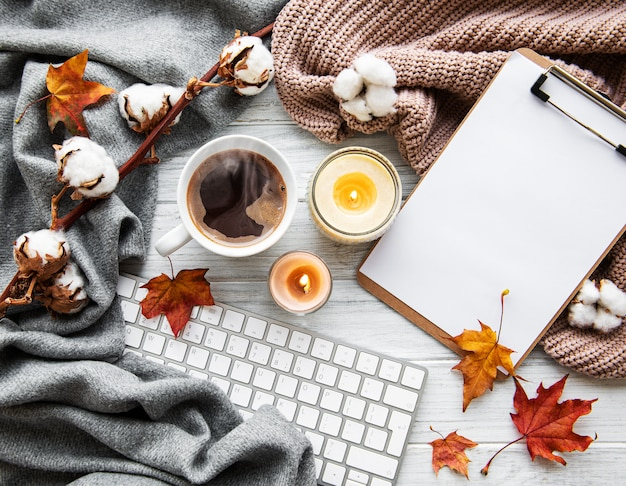 コーヒーカップとキーボードで秋の家居心地の良い組成