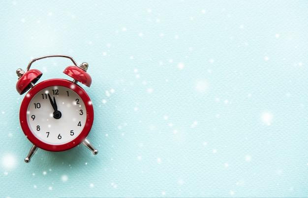 青い雪の背景の目覚まし時計