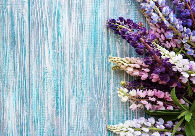 青い木製の背景にピンクと紫のルピナスの花
