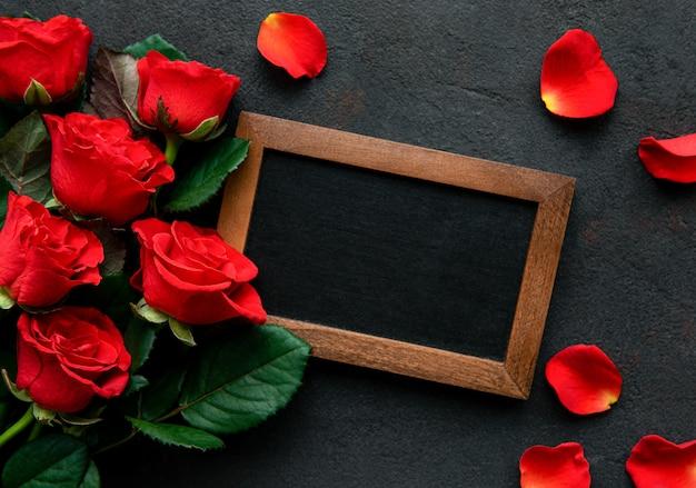 赤いバラと黒板