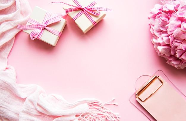 クリップボード、ギフト、ピンクの背景の花のホームフェミニンデスク