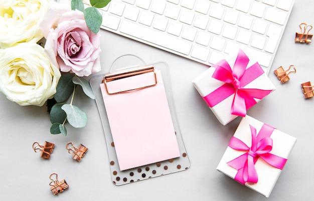 花、ピンクのギフトボックス、キーボード、トップビューで空のクリップボード