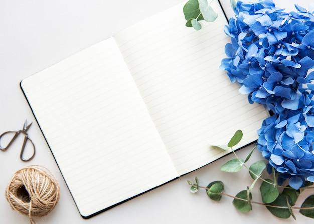 青い花を持つ白いノートブックを開く