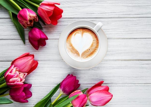 Чашка кофе с латте арт и розовые тюльпаны на деревянный стол. вид сверху, плоская планировка.