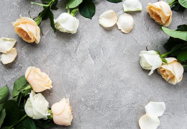 石の背景に黄色と白のバラ