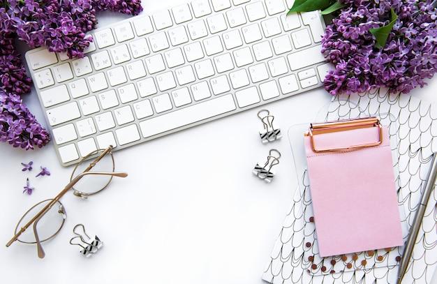フラット横たわっていた、トップビューのオフィステーブルデスク。キーボード、ライラック色の花、白い背景の上の事務用品とワークスペース。