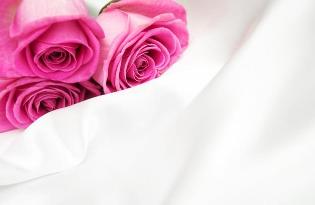 白い絹の背景にバラ