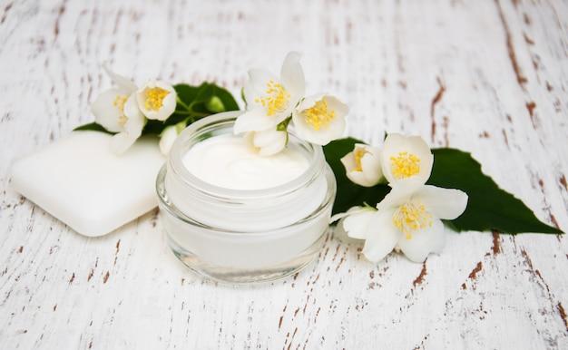 白い木製の背景にジャスミンの花を持つ顔とボディクリームの保湿剤