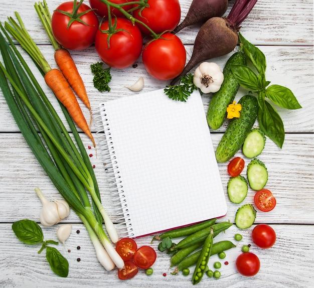 Концепция планирования рецептов с сырыми овощами и ингредиентами