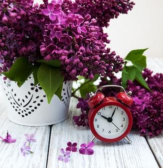 目覚まし時計とライラックの花