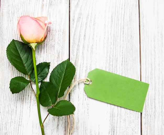 Розовая роза и зеленая бирка