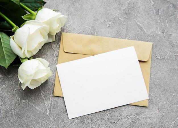 Белые розы и поздравительная открытка