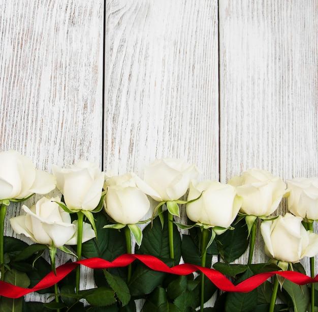 木製のテーブルの上の白いバラ