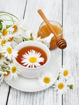 カモミールの花とハーブティーのカップ