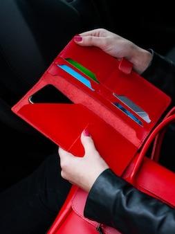 手に赤い革の財布