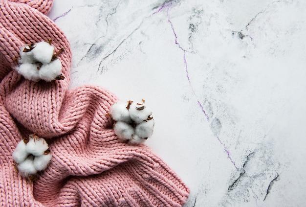 ピンクのニットセーターとコットンの花