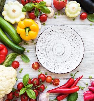 Пустая тарелка и свежие овощи