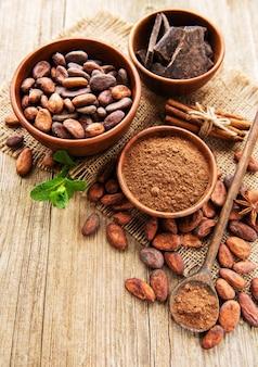 天然ココアパウダー、チョコレート、ココア豆、木製の背景