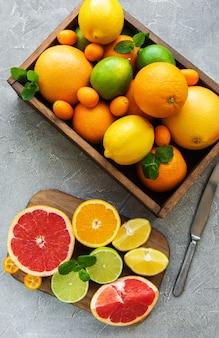 Коробка с цитрусовыми свежими фруктами на бетонном фоне