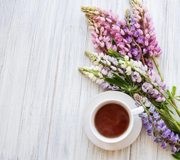 Розовые и фиолетовые цветы люпина и чашка чая вид сверху