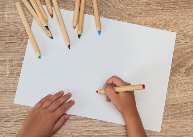 Маленькая девочка, рисование на фоне бумаги