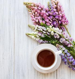 Розовые и фиолетовые цветы люпина и чашка чая