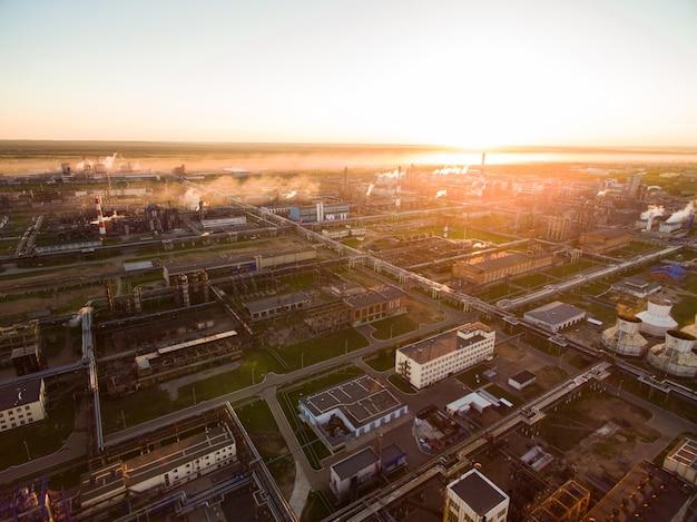 Огромный нефтеперерабатывающий завод с металлическими конструкциями, трубами и комплексом перегонки на закате. с высоты птичьего полета