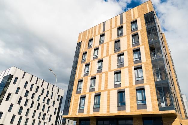白と茶色の建物は現代的なスタイルで作られています。一番下の芝生と木々。