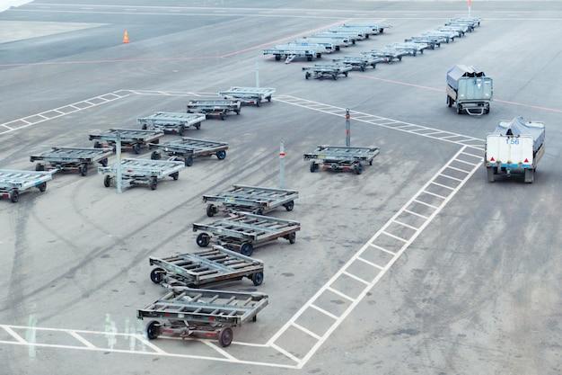アスファルトの上の空の空港荷物用トロリー