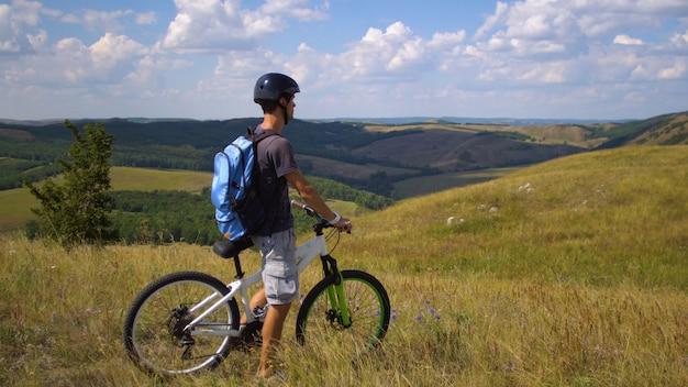 雲と空を背景の緑の丘の間で自転車に乗って若い男