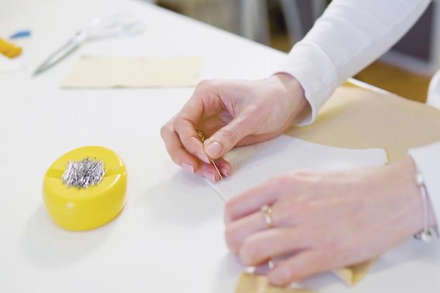 女性フリーランサーまたはファッションデザイナーまたはテーラーのワークショップでカラフルなファブリックのデザインやドラフトに取り組んで