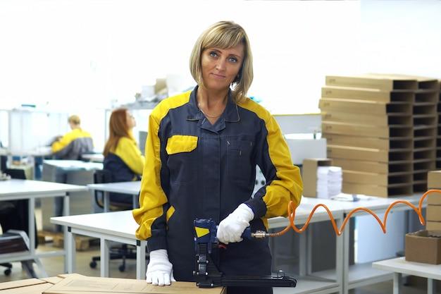 電気製品の生産工場で生産包装ラインの近くに立っている女性工場労働者の肖像画。彼女の手で銃を梱包し、カートンを梱包するためのホッチキス