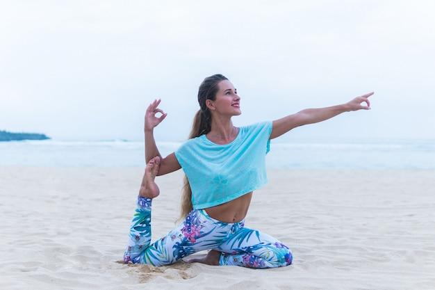 ビーチでヨガの練習若い健康な女性